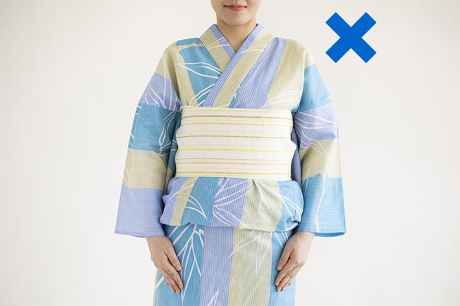 水色の浴衣に黄色の帯を締めた女性