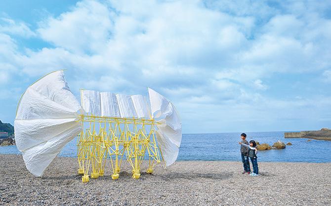 白い和紙と黄色い骨組みで作られたアート作品